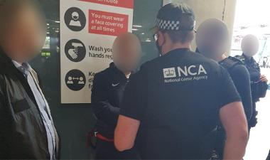 Image showing arrested individual alongside NCA officers.
