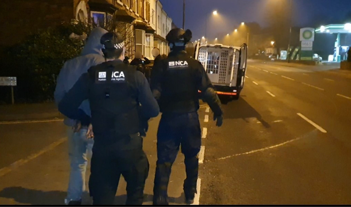 Image showing NCA officers making an arrest in a residential area.
