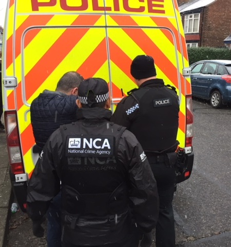 two officers arresting suspect next to police van